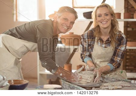Portrait of male potter assisting female potter in pottery workshop
