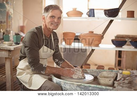 Portrait of smiling male potter making pot in pottery workshop