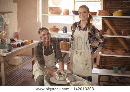 Portrait of male potter assisting female potter in pottery workshop