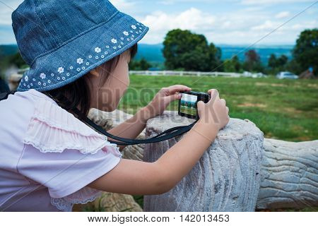 Side view of asian girl with camera at park . Children were photographed views. Child relaxing outdoors at the daytime travel on vacation.
