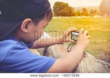 Side view of asian boy with camera at park . Children were photographed views. Child relaxing outdoors with bright sunlight at the daytime travel on vacation. Vintage tone.