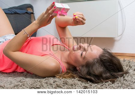 Girl Lying On The Carpet With Present Box