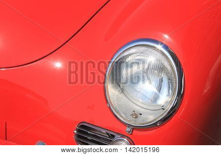 Round automotive headlamp of expensive vintage luxury red car close-up