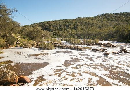 Bell Rapids white waters where the Swan and Avon Rivers intersect under a blue sky with greenery in the Swan Valley in Western Australia.