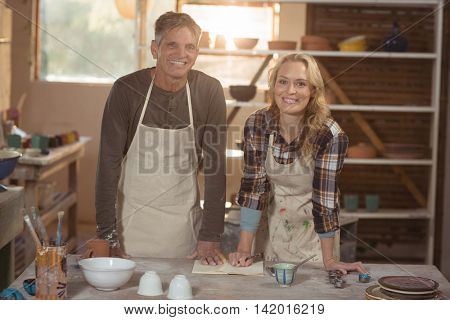 Portrait of smiling potters writing in book at pottery workshop