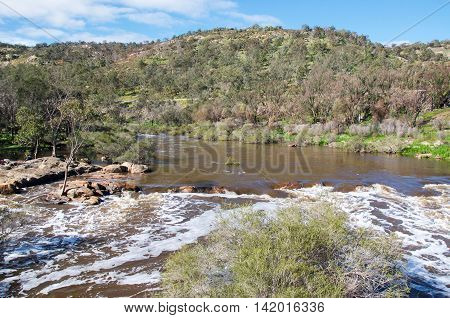 Bell Rapids of the Swan and Avon River intersection with lush hills under a blue sky with clouds in the Swan Valley in Western Australia.