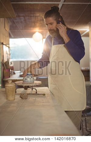 Male potter talking on mobile phone in pottery workshop