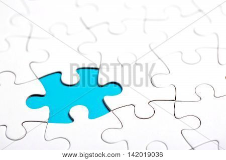 White puzzle with missing part on blue background. Business concept