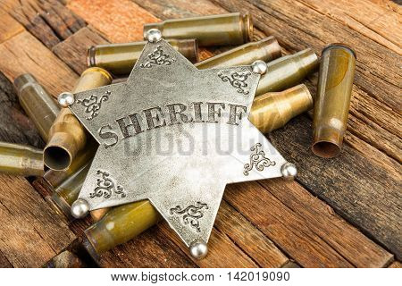 Sheriff badge and bullets shell on wooden background.  Stock image macro.