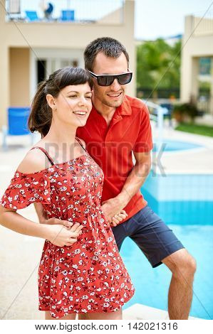 couple standing near the pool. man wearing in red polo shirt and sunglass. loving newlywed couple embracing