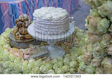 Beautiful wedding cake surrounded by roses. Decoration