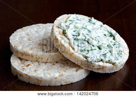 Pile Of Three Puffed Rice Cakes Isolated On Dark Wood. With Chive And Herb Spread.