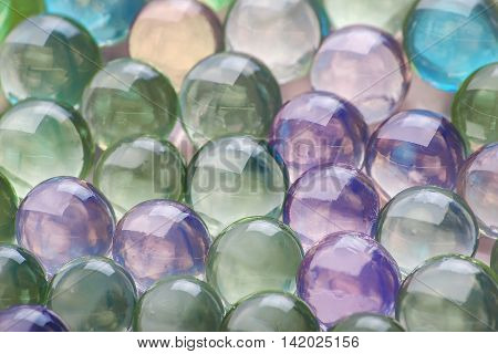 Colored hydrogel balls with shining light on them.