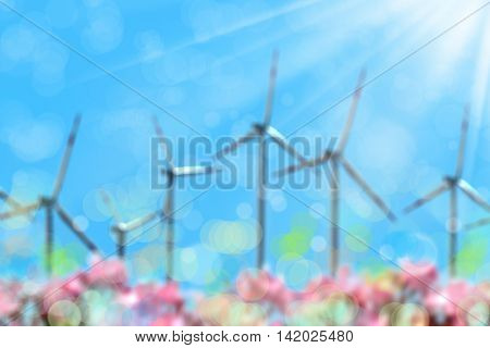 blurry background image of wind turbines over sunny sky