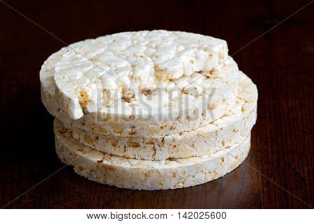 Stack Of Puffed Rice Cakes Isolated On Dark Wood.