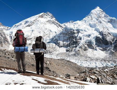 view of Mount Everest Lhotse and Nuptse from Pumo Ri base camp with two tourists on the way to base camp Sagarmatha national park Khumbu valley - Nepal