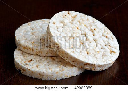 Pile Of Three Puffed Rice Cakes Isolated On Dark Wood.