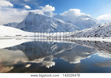 Panoramic view of Annapurna 3 III and Ganggapurna mirroring in Ice Lake or Kicho Tal Annapurna range way to Thorung La pass Annapurna circuit trek Nepal
