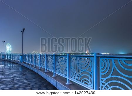 a walking bridge over rier with city skyline background,tianjin china.
