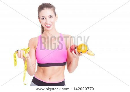 Female at gym holding yellow tape line and fruits isolated on white background with copy text space