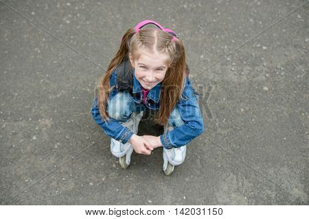 funny little girl in denim jacket squarted down on rollers with backpack