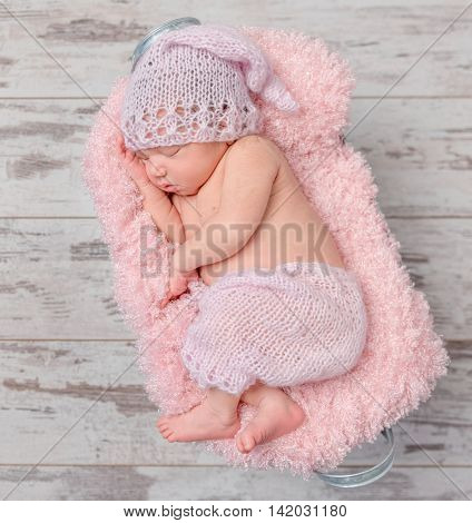 cute newborn baby girl in a pink hat sleeping