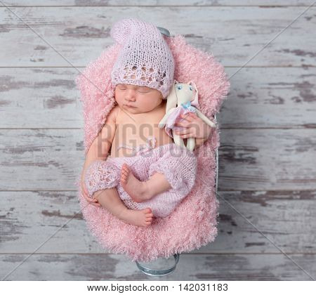 newborn baby girl in a pink hat sleeping with a toy hare