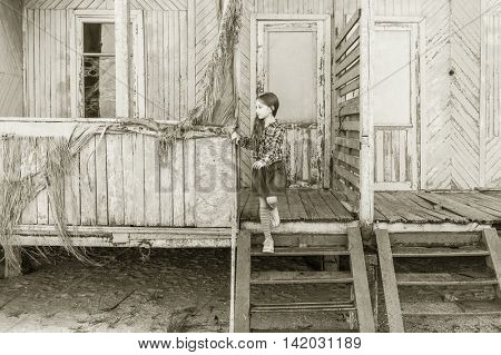 little girl standing on stairs of old wooden bungalow, black and white photo