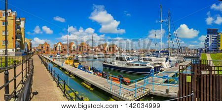 Panoramic view of Sovereign Harbour Marina with moored yachts and luxury houses. Eastbourne, East Sussex, England