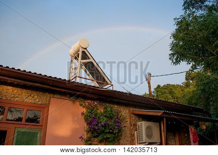 solar cell a building and a rainbow in the background of the clear sky