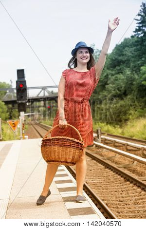 young woman in red dress with basket standing on platform at train station and waving to somebody