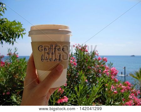 woman's hand holds a coffee Cup that says