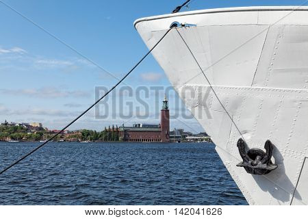 Stockholm view with an anchored ship and town hall on background. Travel concept with these two symbols of the capital city of Sweden.