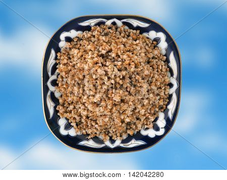 Beautiful dish with buckwheat on a blue background. View from above
