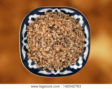 Beautiful dish with buckwheat on a gold background. View from above