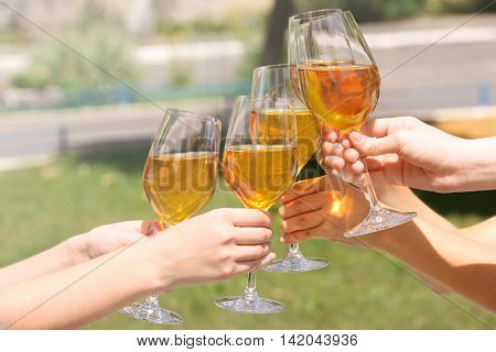 Female hands clinking glasses with white wine outdoors