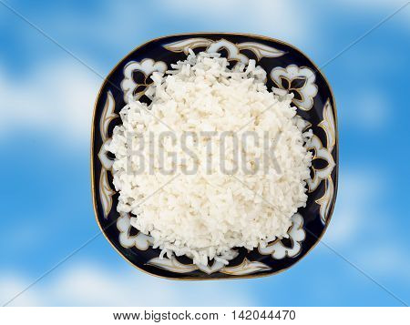 Beautiful dish with boiled rice on a blue background. View from above
