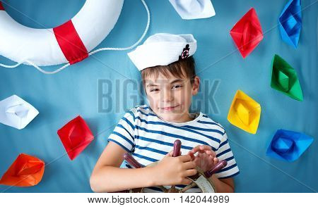seven years old boy playing in sailor hat. Child with a steering wheel and paper ships on blue background