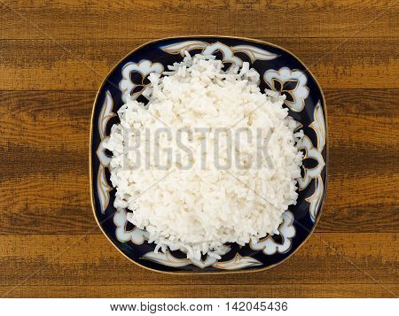 Beautiful dish with boiled rice on a wooden table. View from above