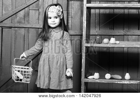 Little girl with plastic vegetables and fruits. Healthy food game kindergarden black and white