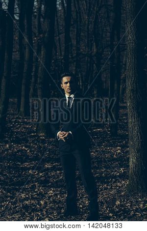 Man young handsome elegant model in suit with skinny necktie looks in camera poses outdoor in woods on woodland landscape background