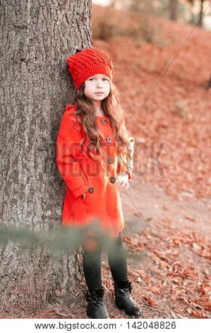 Stylish baby girl 3-4 year old posing outdoors. Wearing trendy winter coat and knitted hat outdoors. Looking at camera. Childhood.