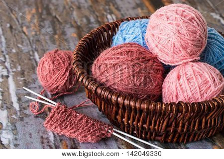 Basket with balls of yarn and knitting a fragment on old wooden table.