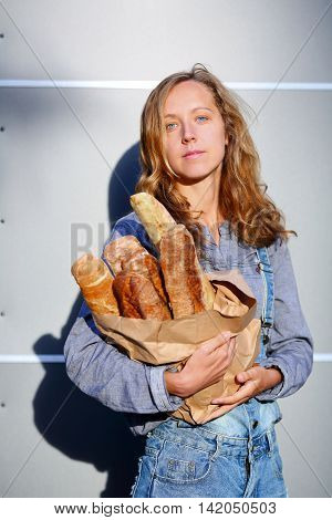 Young Woman Is Holding In Their Hands A Paper Bag With French Baguettes