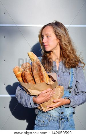Blonde Woman Is Holding In Their Hands A Paper Bag With Fresh French Baguettes