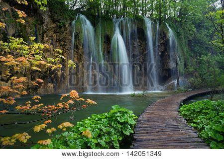 Waterfall down to green lake. Yellow and red maple tree in foreground. Scene in Plitvice Lakes National Park.