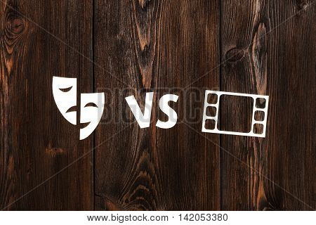 Theatre vs movie. Abstract paper conceptual image on wooden background