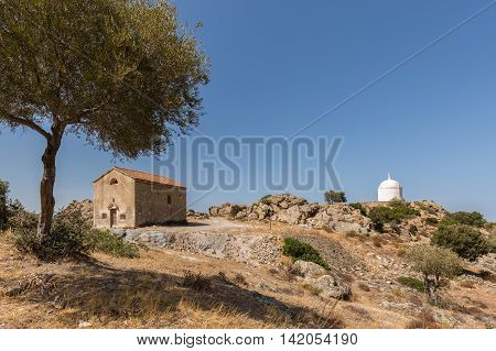 San Sebastiano chapel built in 1819 near Palasca in the Balagne region of Corsica with a large white mausoleum in the background and clear blue sky above