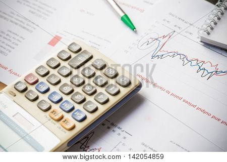 Papers With Graphs Data Calculator And Pen On Wood Table
