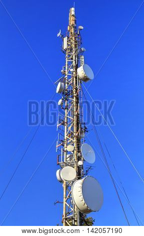 Communication antenna tower on blue sky closeup
